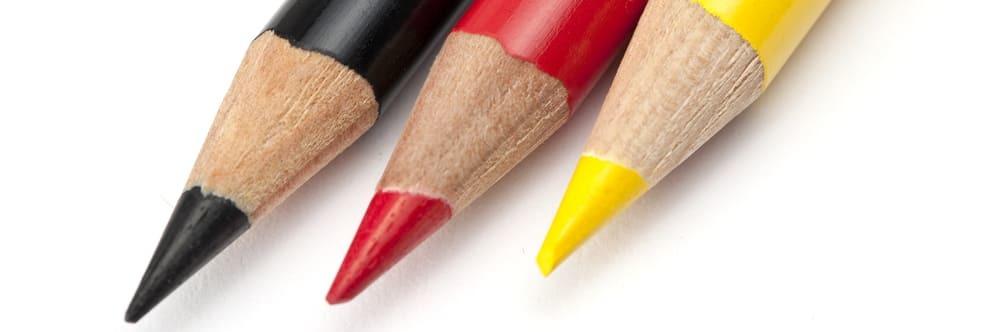 drie pennen in de kleur van de duitse vlag als symbool voor vertalingen nederlands - duits